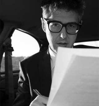 image of Ira Glass writing in the car - photo by NANCY UPDIKE